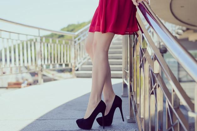 Foto de garota com vestido vermelho, pernas, salto alto e escada