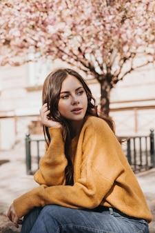Foto de garota de suéter amarelo sobre fundo de sakura. mulher de jeans posando do lado de fora. foto de uma senhora vestida com estilo, aproveitando o clima da primavera