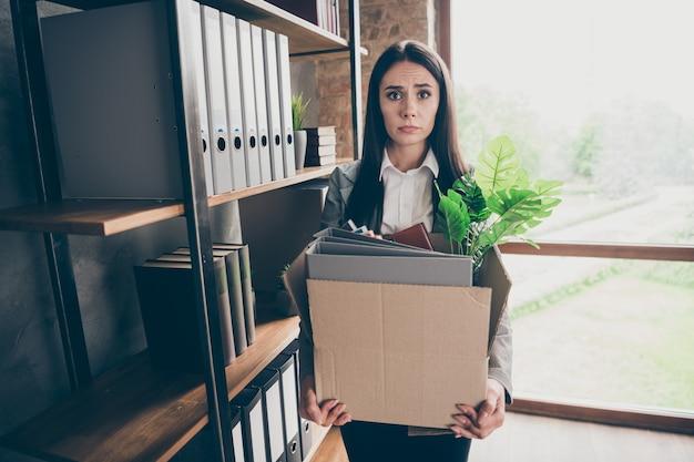 Foto de garota estressada e frustrada e deprimida especialista ceo perder emprego segurar caixa de papelão com pastas e usar paletó blazer na estação de trabalho