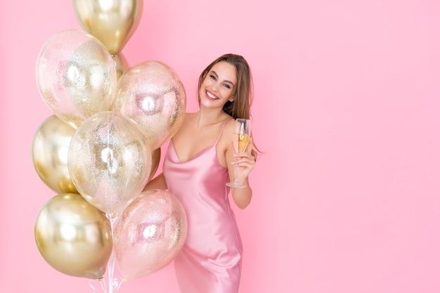 Foto de garota feliz segurando uma taça de champanhe e muitos balões de ar vieram para a celebração da festa
