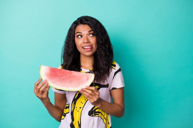 Foto de garota inspirada com olhar de espaço vazio segurar melancia lamber língua lábios pensar isolado sobre fundo de cor turquesa
