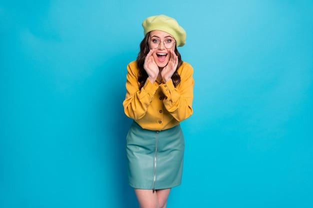 Foto de garota louca surpresa, grito, mão, boca, compartilhe informações confidenciais incríveis, use roupas amarelas e lindas toucas isoladas sobre fundo de cor azul
