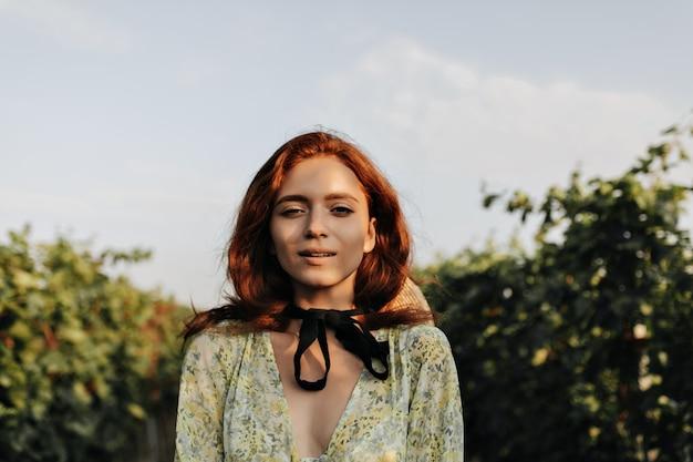Foto de garota na moda com penteado ruivo brilhante e bandagem no pescoço com roupas leves e modernas, olhando para a frente ao ar livre