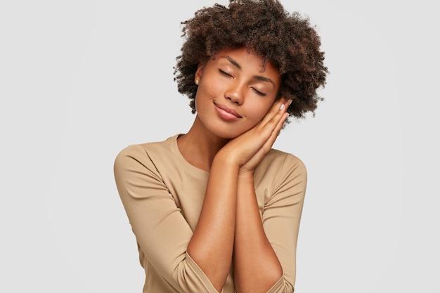 Foto de garota negra cansada cochilando, posa com as mãos juntas, mantém os olhos fechados, tem sonhos positivos, fica feliz em descansar