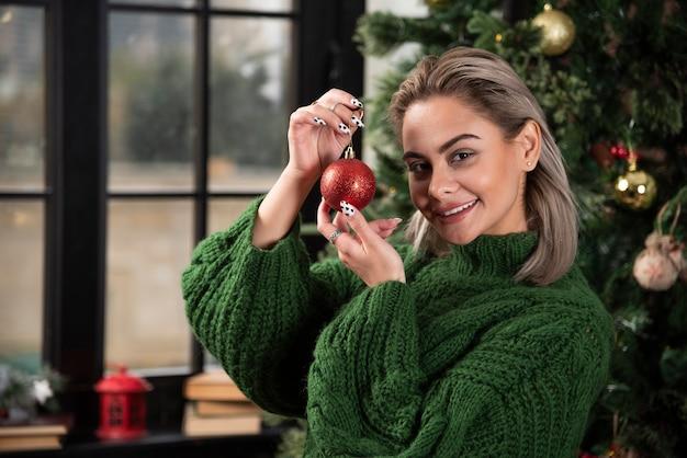 Foto de garota positiva segurando uma bola vermelha de natal