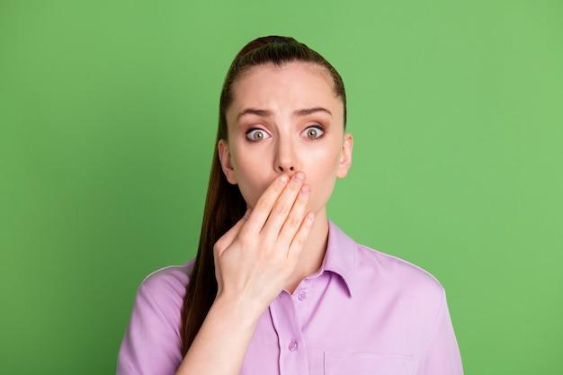 Foto de garota surpresa e frustrada compartilhar segredo de amigos falhou fechar tampa mão boca lábios vestindo camisa lilás violeta isolada sobre fundo de cor verde