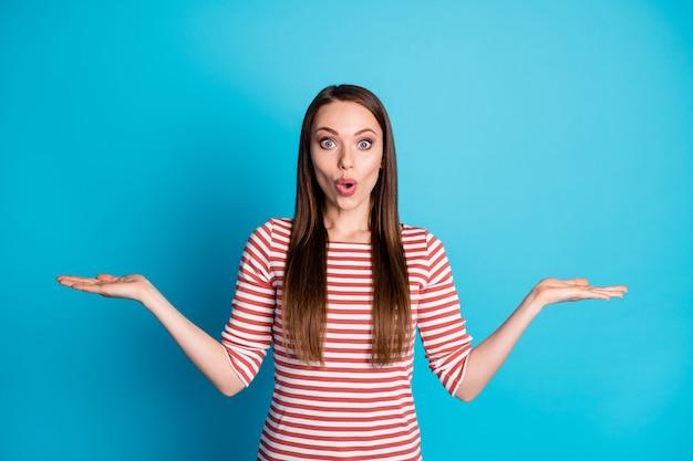 Foto de garota surpresa, segurando a mão, objeto impressionado, anúncios de produtos, roupas promocionais, roupas bonitas, isoladas sobre fundo de cor azul