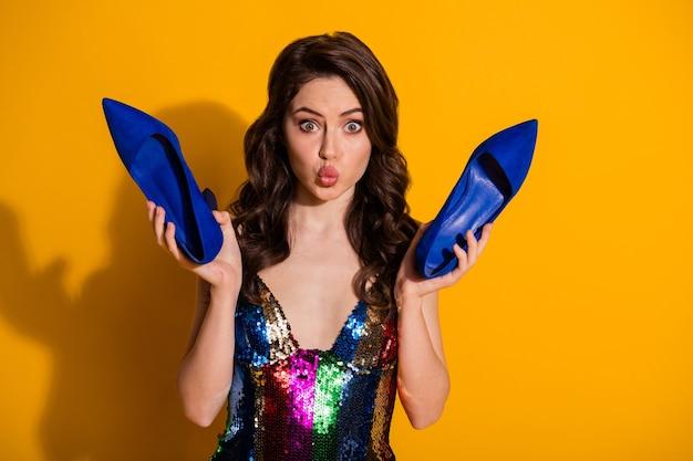 Foto de garota surpresa segurando estiletes azuis enviar beijo no ar e usar saia brilhante isolada sobre fundo de cor brilhante
