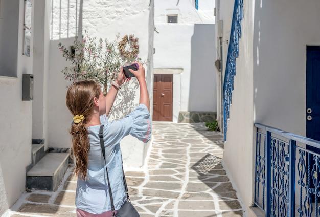 Foto de garota tomada da arquitetura rústica grega no smartphone