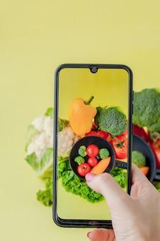 Foto de garota tomada de comida vegetariana na mesa com seu smartphone