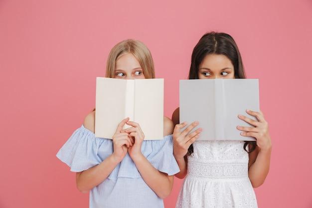 Foto de garotas europeias animadas ou surpresas de 8 a 10 anos usando vestidos cobrindo o rosto com livros, isolada sobre um fundo rosa