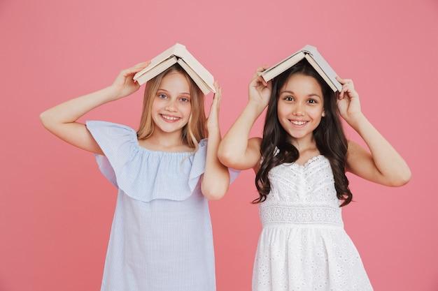 Foto de garotas europeias felizes usando vestidos segurando livros na cabeça enquanto sorriem para a câmera, isoladas sobre fundo rosa