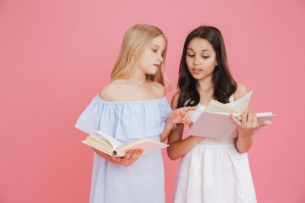 Foto de garotas morenas e loiras espertas usando vestidos segurando e lendo livros junto com interesses, isolada sobre fundo rosa