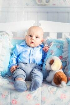 Foto de garotinho com roupas azuis sentado no sofá