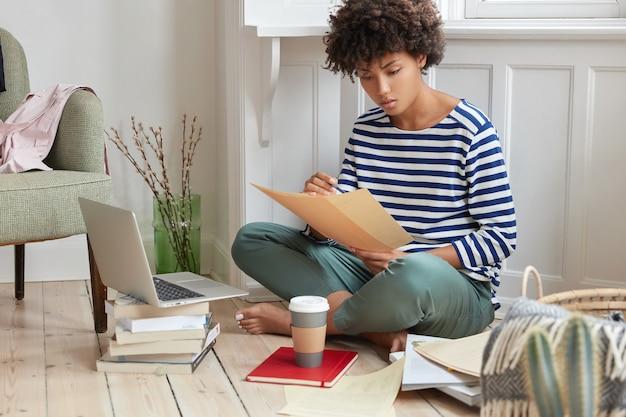 Foto de gerente financeiro cria relatório em local aconchegante, senta-se com as pernas cruzadas perto de um laptop aberto, segura papéis, desenvolve estratégia para fazer negócios