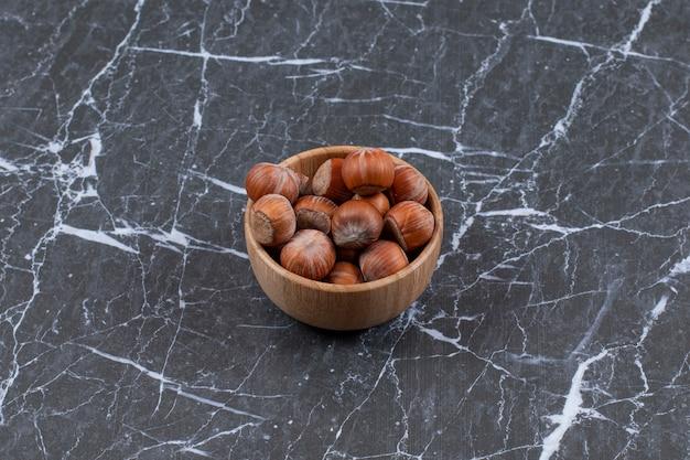 Foto de grande angular de deliciosas avelãs em uma tigela de madeira.
