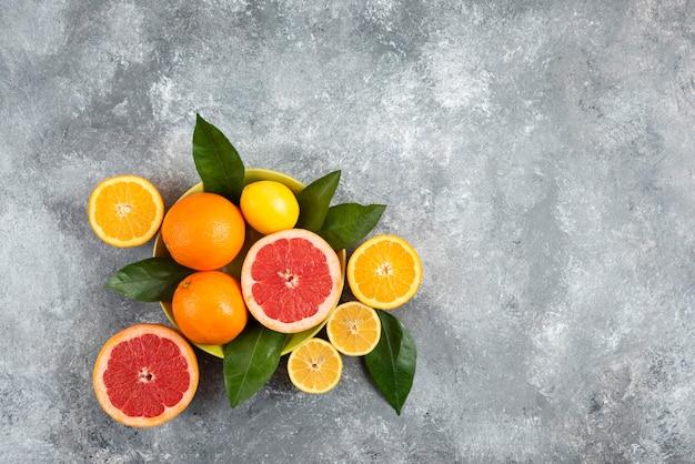 Foto de grande angular de frutas cítricas frescas sobre uma superfície cinza.