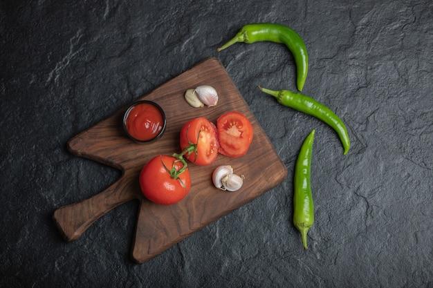 Foto de grande angular de tomates maduros com alho e ketchup na tábua de madeira e pimenta verde sobre fundo preto.