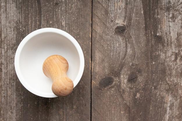 Foto de grande angular de um almofariz e pilão em uma superfície de madeira