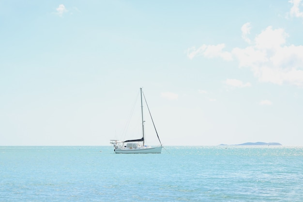 Foto de grande angular de um barco no topo de um oceano sob um céu claro e ensolarado