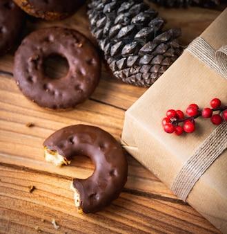 Foto de grande angular de um donut de chocolate comido pela metade ao lado de um presente embrulhado e uma pinha