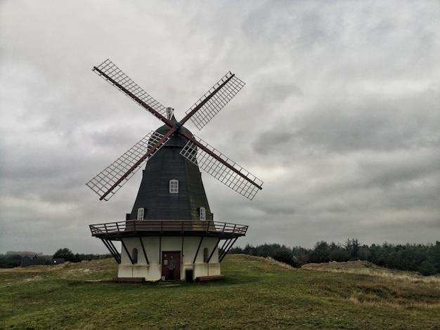 Foto de grande angular de um moinho de vento sob um céu cheio de nuvens
