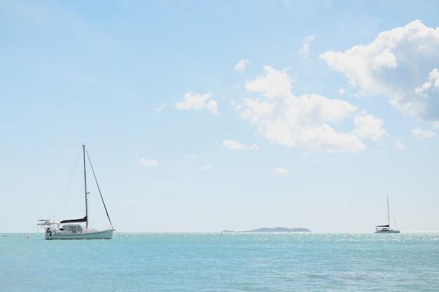 Foto de grande angular de um oceano com barcos no topo sob um céu claro,