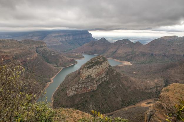 Foto de grande angular de um pequeno lago cercado por montanhas e vegetação durante o dia