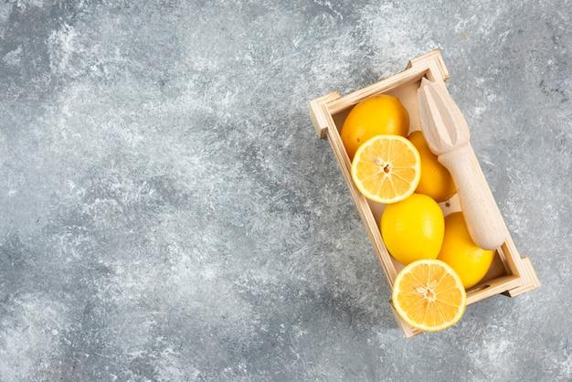 Foto de grande angular de uma caixa de madeira cheia de limões frescos.