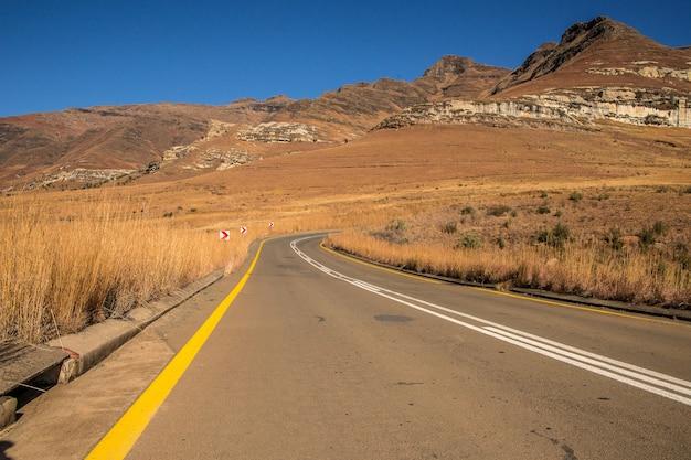 Foto de grande angular de uma estrada indo em uma montanha cercada por arbustos e grama seca
