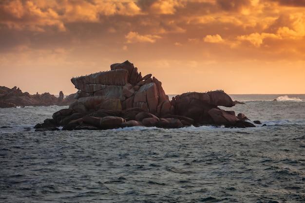 Foto de grande angular de uma ilha de penhascos cercada pela água durante o pôr do sol