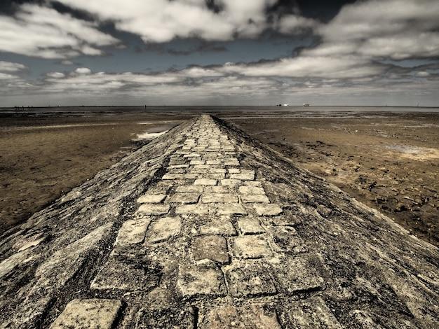 Foto de grande angular de uma passarela de pedra cercada pelo deserto