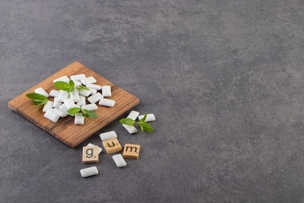 Foto de grande angular de uma pilha de gomas brancas com folhas de hortelã em uma tigela de madeira