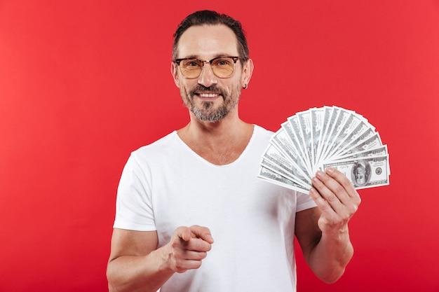 Foto de homem adulto 30 anos de camiseta branca casual usando óculos, sorrindo e apontando o dedo na câmera enquanto segura ventilador de dinheiro dólar em dinheiro, isolado sobre fundo vermelho
