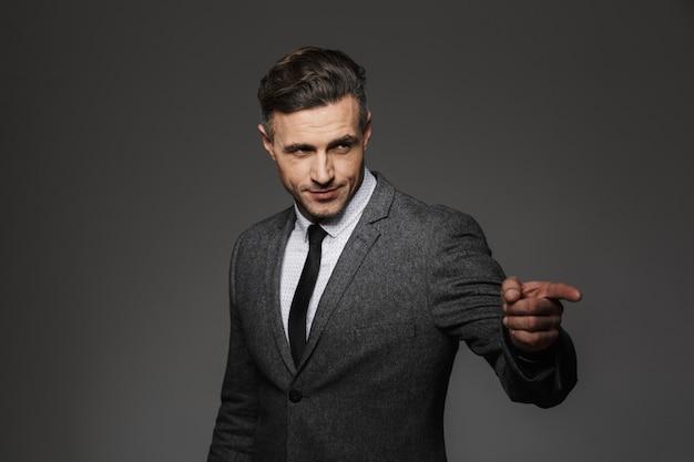 Foto de homem adulto com aparência de conteúdo em terno e gravata apontando o dedo de lado na copyspace, isolada sobre uma parede cinza