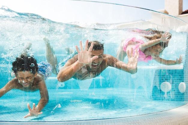 Foto de homem adulto com crianças mergulhando e nadando debaixo d'água em uma piscina transparente, durante as férias de verão