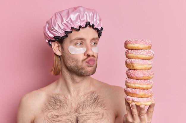 Foto de homem adulto em topless com os lábios dobrados olha para rosquinhas apetitosas aplica adesivos para reduzir as olheiras sob os olhos e usa touca de banho com ombros nus contra a parede rosa