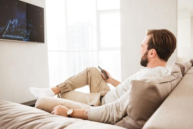 Foto de homem adulto relaxado em roupas casuais, sentado no sofá na sala de estar e assistindo tv