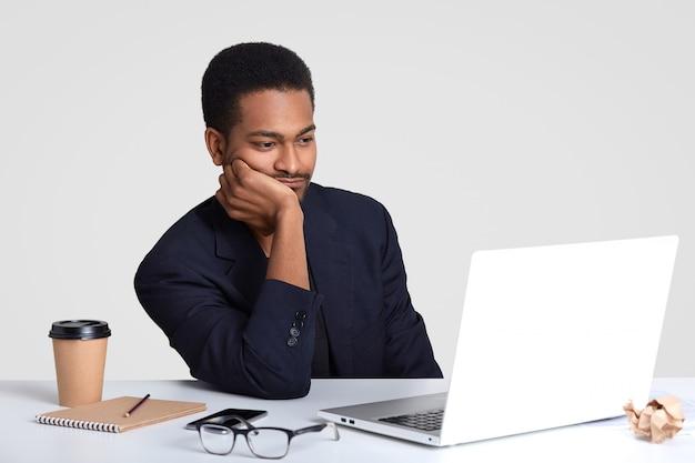 Foto de homem afro-americano de pele escura mantém a mão na bochecha, assiste atentamente o vídeo tutorial, se prepara para uma reunião de negócios, tem o bloco de notas e caneta na mesa branca, veste terno formal, posa em recinto fechado