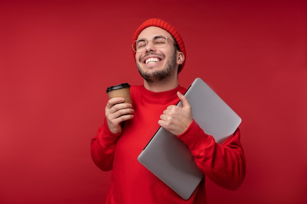 Foto de homem atraente com barba de óculos e roupas vermelhas. homem feliz segura laptop e café é bom, isolado sobre fundo vermelho.