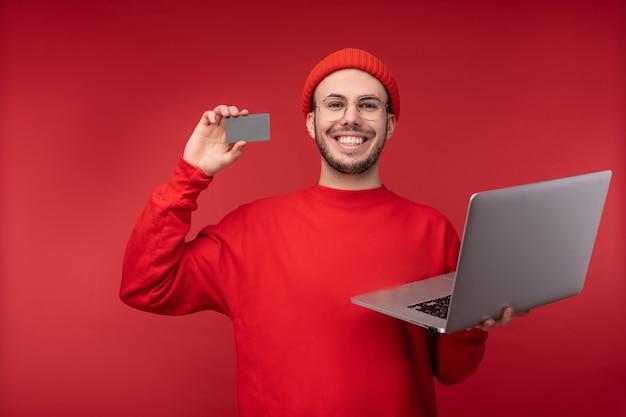 Foto de homem atraente com barba de óculos e roupas vermelhas. homem feliz sorri, tem cartão de crédito e laptop, isolado sobre fundo vermelho.