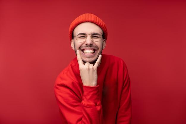 Foto de homem atraente com barba de óculos e roupas vermelhas. macho mostra gestos de rock and roll e sorrisos, isolados sobre fundo vermelho.