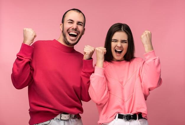 Foto de homem atraente com barba em roupas vermelhas e mulher de sorriso rosa e se alegrar com algo. casal parece engraçado, isolado sobre fundo rosa.