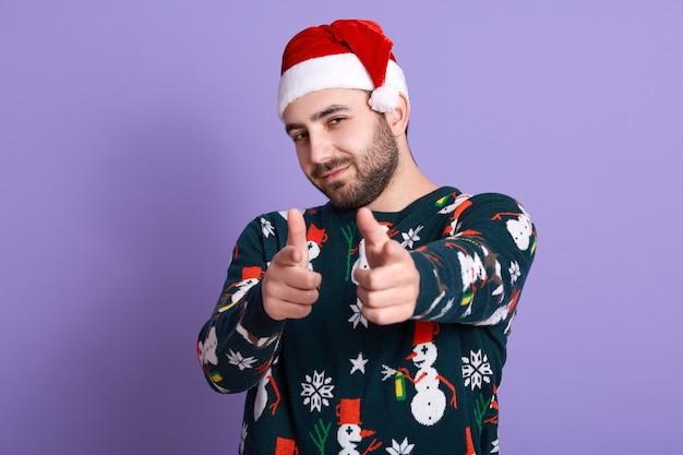 Foto de homem barbudo alegre usando chapéu de papai noel e camisola engraçada com bonecos de neve