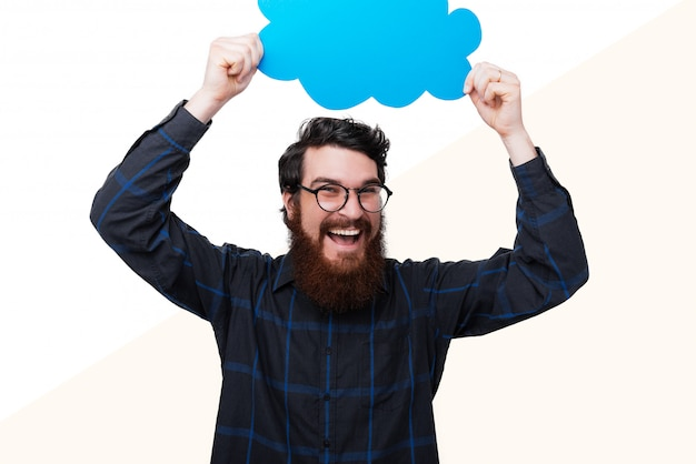 Foto de homem barbudo feliz segurando uma bolha spech na cabeça, de pé em branco