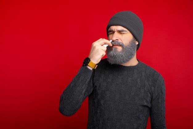 Foto de homem barbudo hispter com um spray nasal, alergia no nariz
