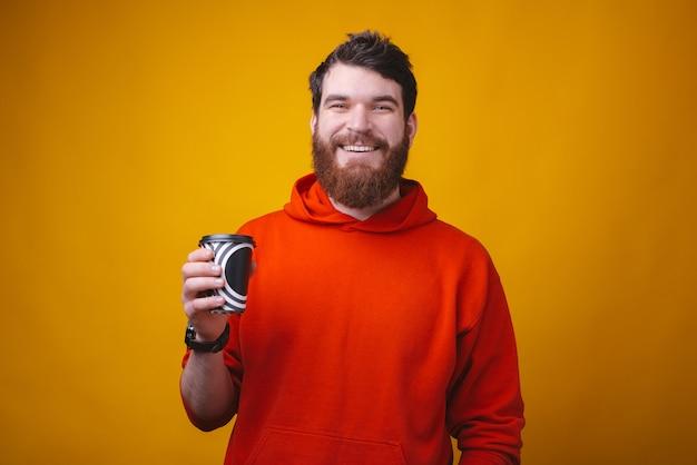 Foto de homem barbudo no espaço amarelo está segurando um papel de café preto e branco para ir a xícara.
