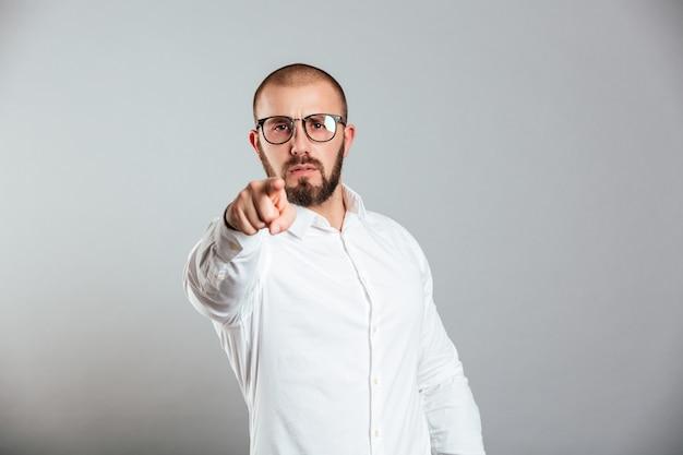 Foto de homem barbudo persistente na camisa branca e óculos, gesticulando no dedo indicador da câmera, ou seja, ei você, isolado sobre a parede cinza