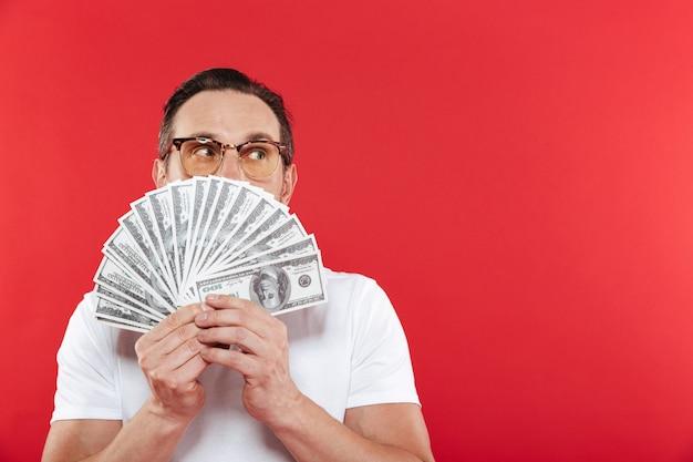 Foto de homem bem sucedido em camiseta branca casual, cobrindo o rosto com muito dinheiro na nota de dólar, segurando nas mãos e olhando de lado na copyspace, isolada sobre parede vermelha
