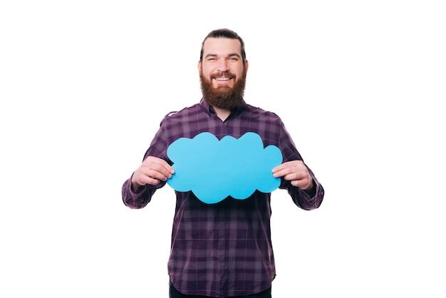 Foto de homem bonito casual segurando uma nuvem azul vazia